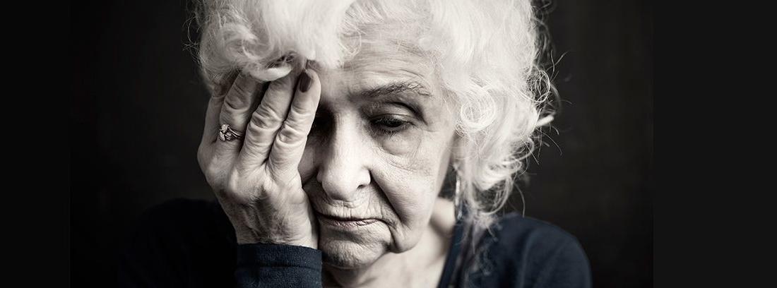 mujer mayor con la mano en la cara en fondo negro