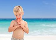 niño en playa con helado