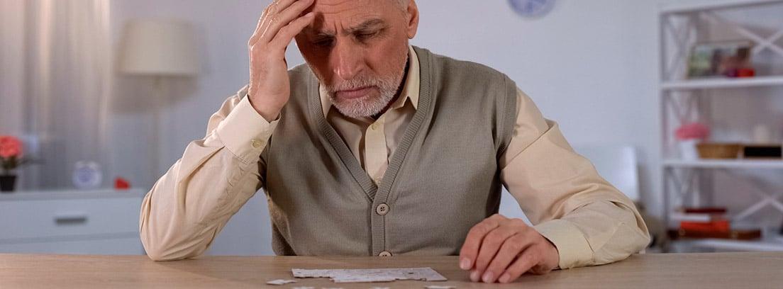 Deterioro cognitivo: hombre mayor pensando como hacer un puzle