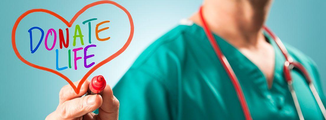 medico pintando un corazón con las palabras donante vivo en inglés