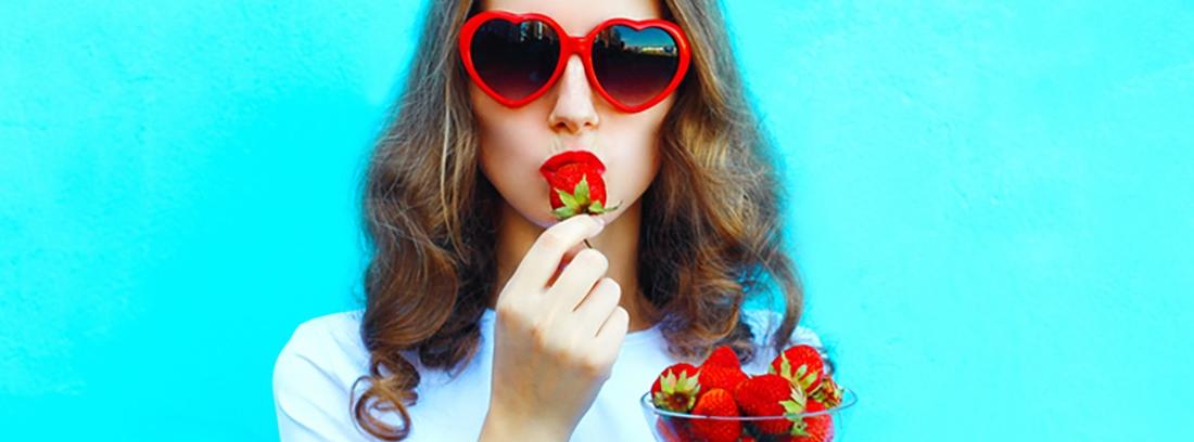 chica con gafas de sol rojas comiendo fresas