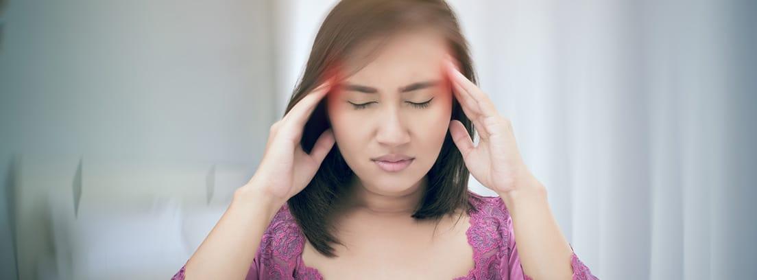 Neuritis vestibular: mujer con las manos sobre las sienes con sensación de vértigo