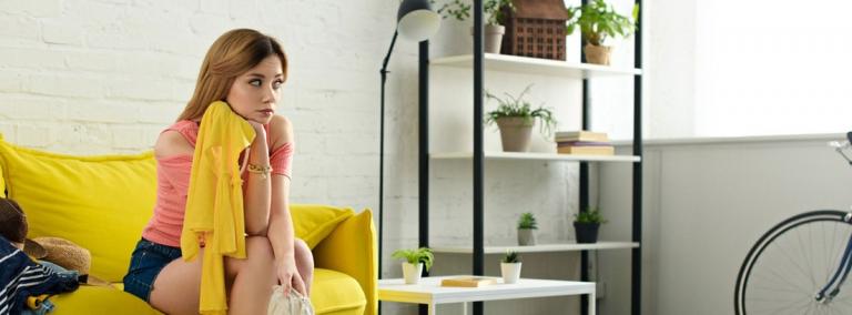 chica sentada en un sofá con cara triste