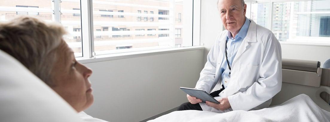 Shock hipovolémico: mujer mayor tendida en cama de hospital conversando con el médico