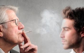 hombre mayor echando humo de tabaco a la cara de un joven