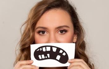 mujer con un dibujo de una dentadura rota tapándose la boca