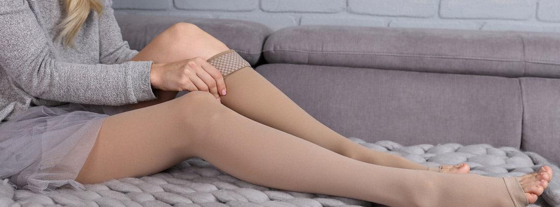 Trombosis venosa superficial: mujer poniendose unas medias elásticas para la prevención de las varices