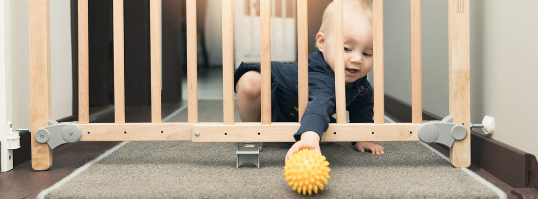 Casa segura para bebés: bebé cogiendo una pelota a través de una vaya de seguridad para escaleras