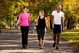dos mujeres y un hombre caminando por un parque