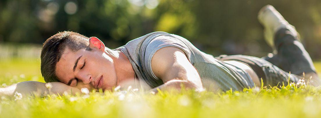 joven tumbado en un parque en primavera