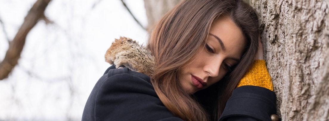 mujer deprimida apoyada en un árbol en otoño