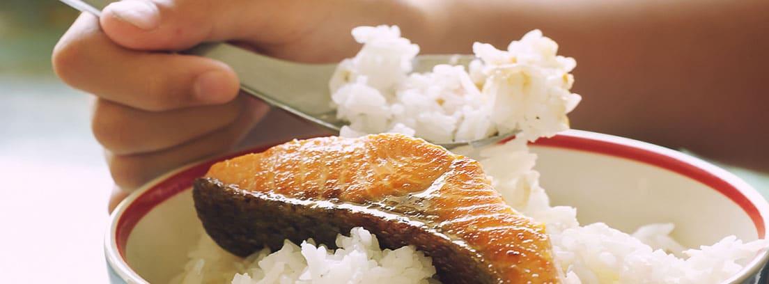 10 Consejos para que los niños coman pescado: niño comiendo salmón con arroz