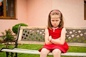 niña enfadada sentada en un banco