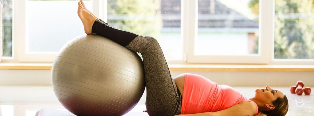Consejos para sobrellevar el calor durante el embarazo:mujer embarazada tumbada realizando ejercicios de piernas con una pelota grande