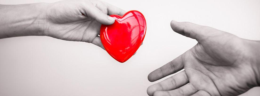 mano donando un corazón rojo a otra mano