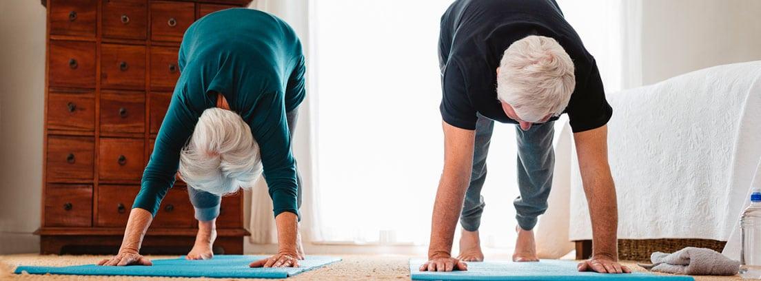 Ejercicio para seniors: pareja de personas mayores practicando ejercicio en el dormitorio
