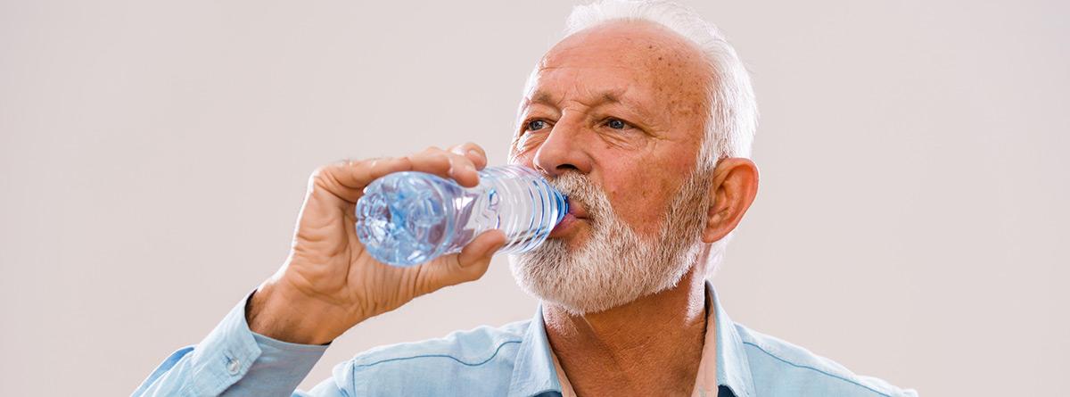 Hidrataci´çon en las personas mayorres: hombre maduro bebiendo un vaso de agua