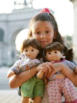 niña con dos muñecas de juguete en la mano