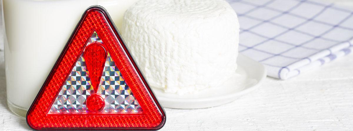 Intolerancia a la lactosa en la osteoporosis: Triangulo en rojo de alerta con productos lácteos