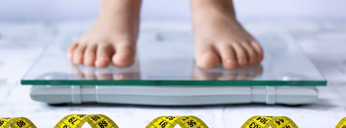 Malnutrición en niños: pies de niño encima de una báscula y trozos de cinta de metro