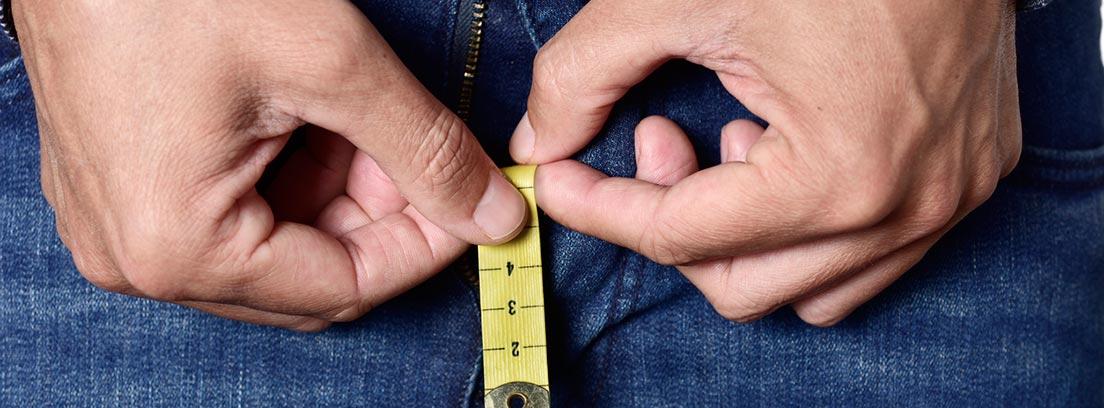 Micropene: hombre con la bragueta del pantalón abierta con un metro en la mano
