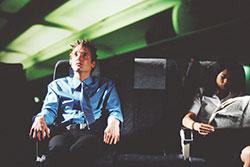 un chico con miedo a volar en un avión junto a una chica relajada