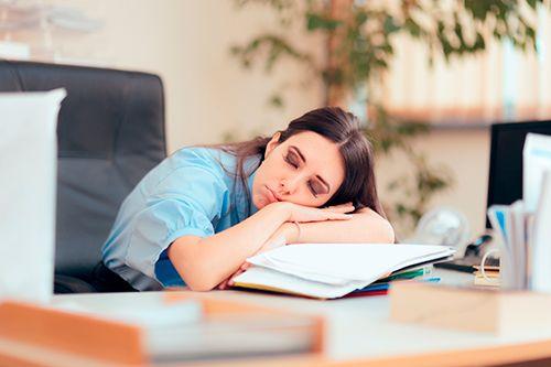 chica joven dormida encima de la mesa de oficina