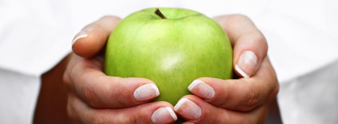 manos sujetando una manzana verde