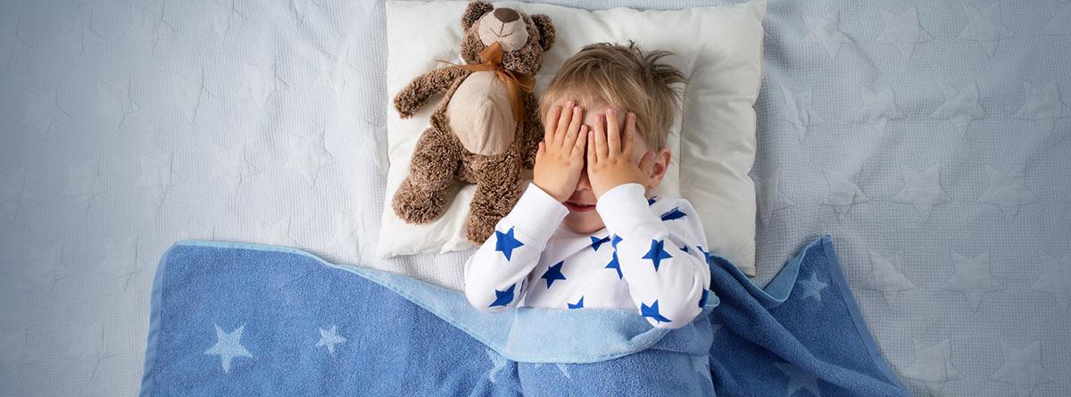 Pesadillas y terrores nocturnos: niño en la cama con las manos tapándose la cara y un osito de peluche a su lado