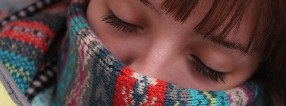 chica con los ojos cerrados y una bufanda hasta la nariz