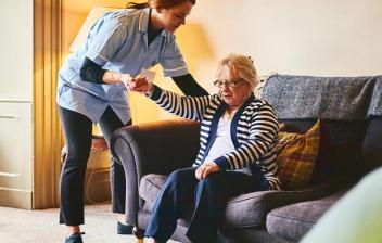 Síndrome de inmovilidad en personas mayores: cuidadora ayudando a levantarse del sofá a una mujer mayor
