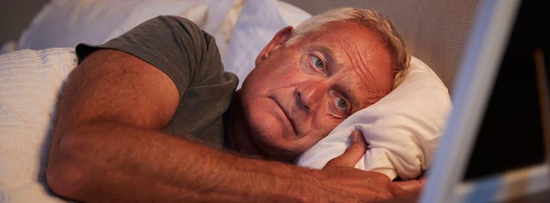 El sueño en las personas con demencia: Hombre Senior triste tumbado en la cama mirando el marco de la foto