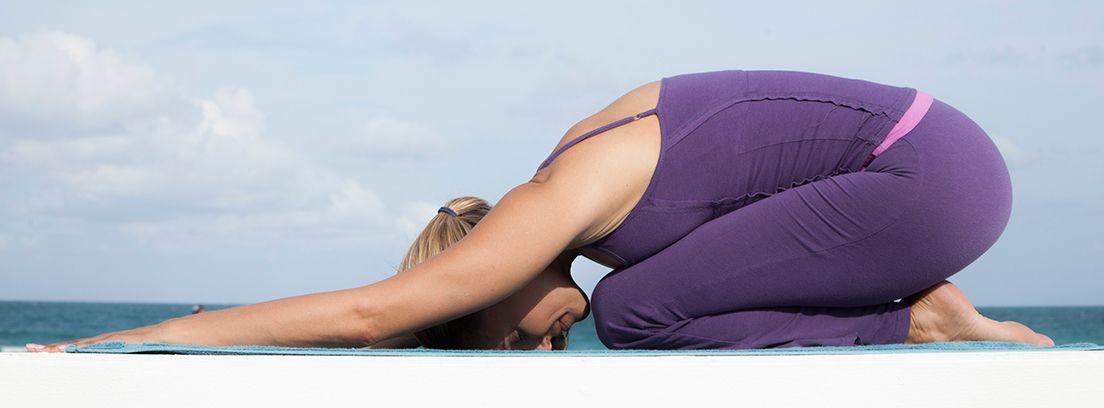 mujer en la playa practicando yoga