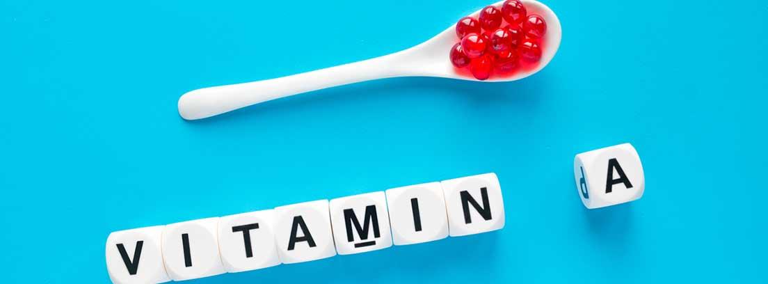 cuchara con cápsulas y cubos blanco con la palabra vitamina A
