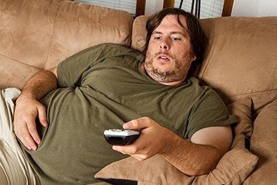hombre sentado en el sofá con el mando a distancia