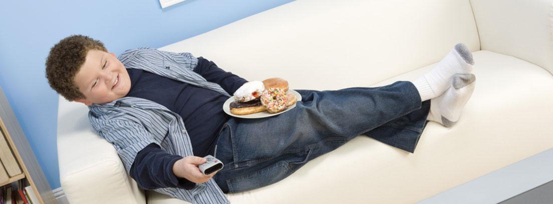 Obesidad infantil y la publicidad niño viendo la tele en el sofá