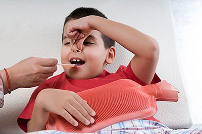 niño tomando medicamento tapándose la nariz