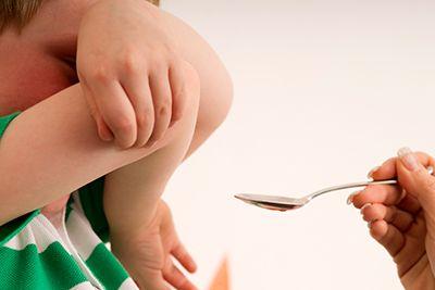 niño con los brazos tapándose la cara para no tomar medicamentos
