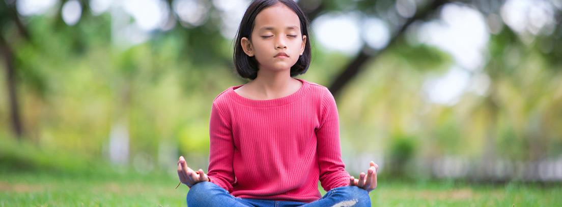 niña practicando meditación al aire libre