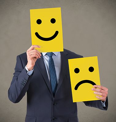 dibujo de cara triste y cara alegre en cartón cogidos por una persona