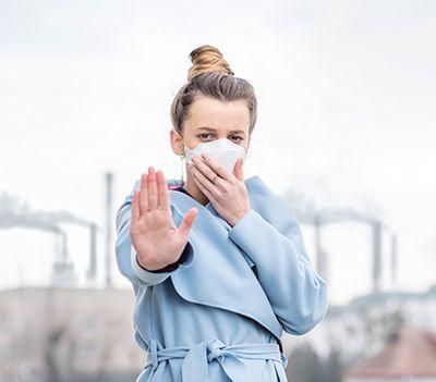 mujer con mascarilla y gabardina delante de chimeneas industriales