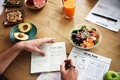 manos escribiendo una dieta encima de una mesa con diferentes alimentos