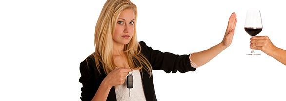 mujer rechazando una copa de vino con las llaves del coche en la mano