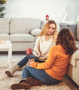 dos mujeres hablando en en suelo con una taza