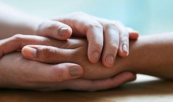manos de persona agarrando la mano de otra