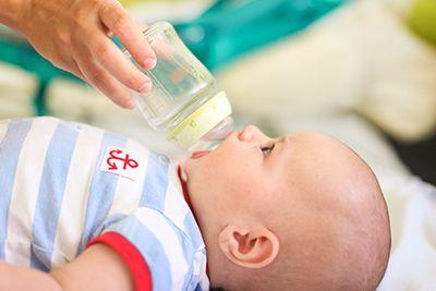 bebé tumbado bebiendo un biberón de agua