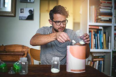 hombre preparando biberón con leche de continuación
