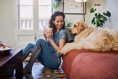 mujer sentada en el suelo y su perro en el sofá