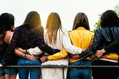 cinco mujeres de espaldas abrazadas