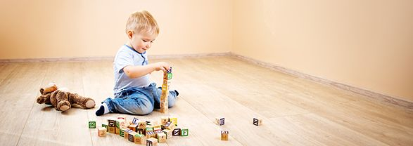 niño sentado en el suelo jugando con cubos de madera